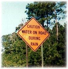 caution water on road during rain sign